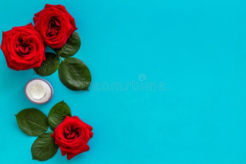 Cosm?tiques organiques naturels avec l'extrait rose sur le copyspace bleu de vue sup?rieure de fond photo stock
