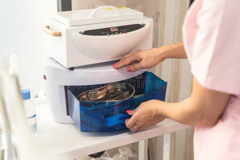 Cosmetólogo coloca as ferramentas de manicura em Esterilizador de Alta Temperatura Limpeza e desinfecção Salão de beleza imagem de stock royalty free