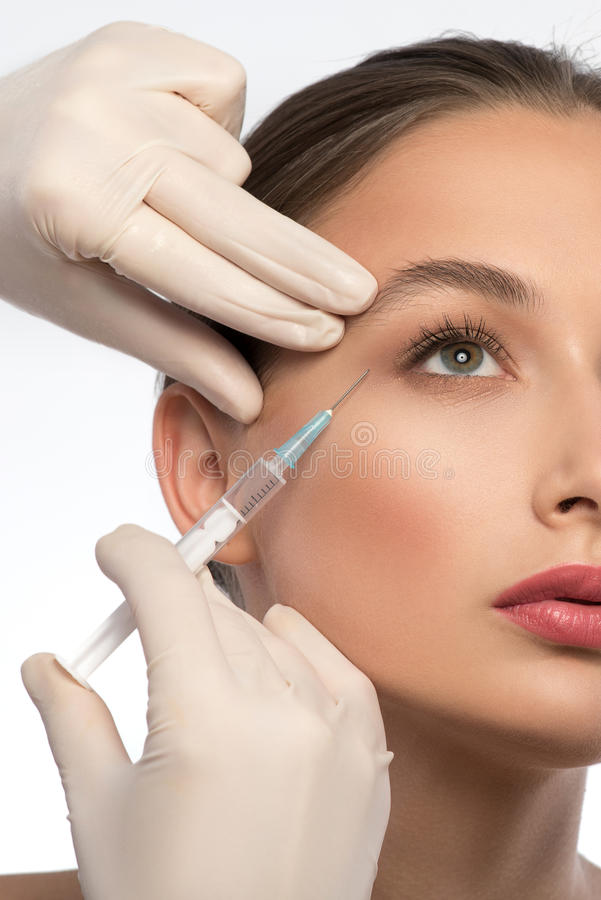 Cosmetólogo experimentado que inyecta la cara de la mujer fotografía de archivo