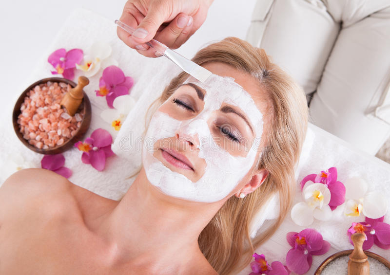 Cosmetólogo que aplica la máscara facial en la cara de la mujer fotos de archivo libres de regalías