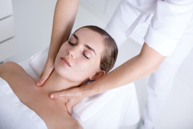 Cosmetólogo que da masajes al cuerpo de la mujer joven imagen de archivo