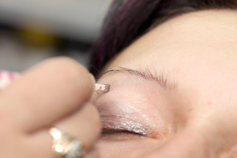 Cosmetólogo que extrae con pinzas las cejas de la mujer en un centro del balneario foto de archivo