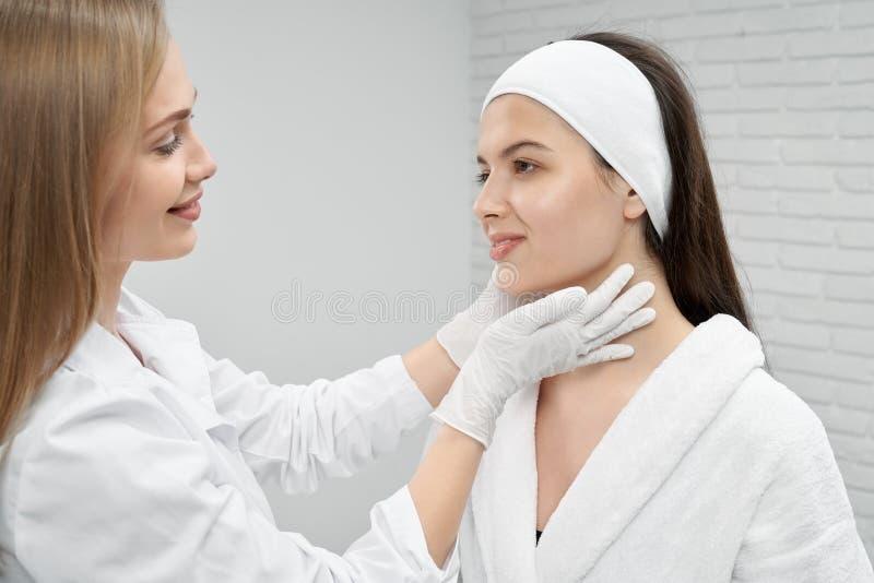 Cosmetólogo que visita del cliente femenino feliz en salón imagenes de archivo