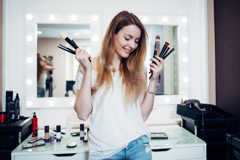 Cosmetólogo tímido joven que presenta con los cepillos del maquillaje fotos de archivo libres de regalías