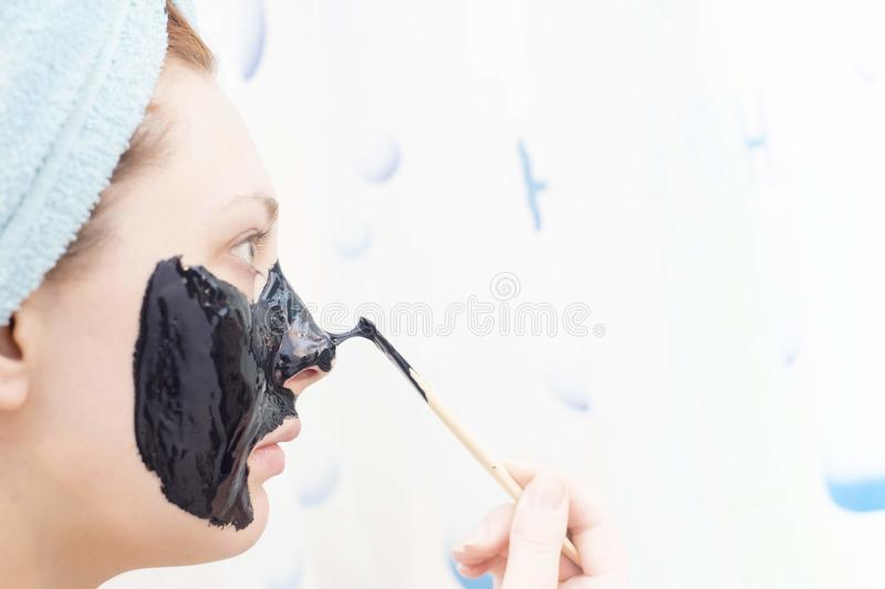 Cosmetic black mask. Woman in the bathroom to put on a cosmetic black mask on white background stock photography