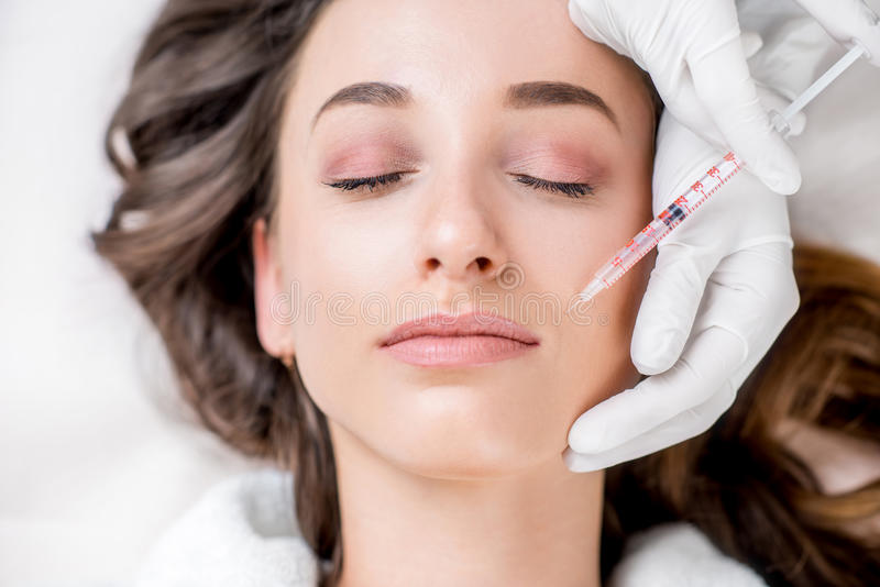 Cosmetic botox injection. Woman receiving a botox injection in the lips zone lying on the medical couch stock photography