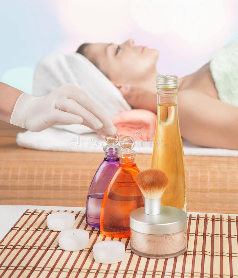 Cosmetic bottle of aromatic massage oil are on the cosmetic table. Young women who expects treatments in the background out of focus royalty free stock image