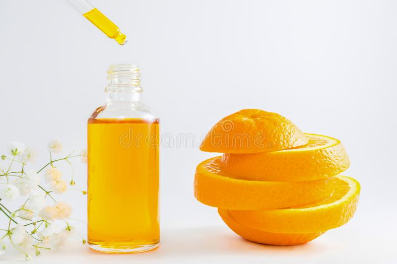 Vitamin C serum in cosmetic bottle with dropper, sliced orange and flowers on white background. Organic SPA cosmetics with herbal. Cosmetic bottle with dropper stock image