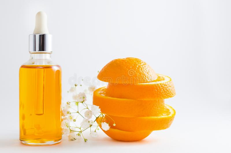 Vitamin C serum in cosmetic bottle with dropper, sliced orange and flowers on white background. Organic SPA cosmetics with herbal. Cosmetic bottle with dropper stock photography