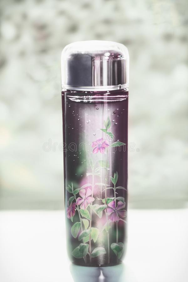 Cosmetic bottle with liquid and little pink flowers. Floral essence, herbal extract toner or perfume on table, front view. Beauty. And modern skin care concept royalty free stock images