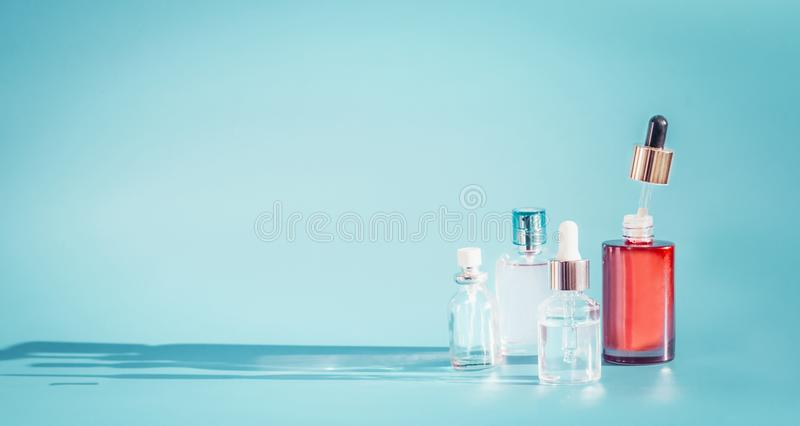 Cosmetic bottle products with liquid, pipette at blue background, front view. Essence, toner or extract serum on table stock image