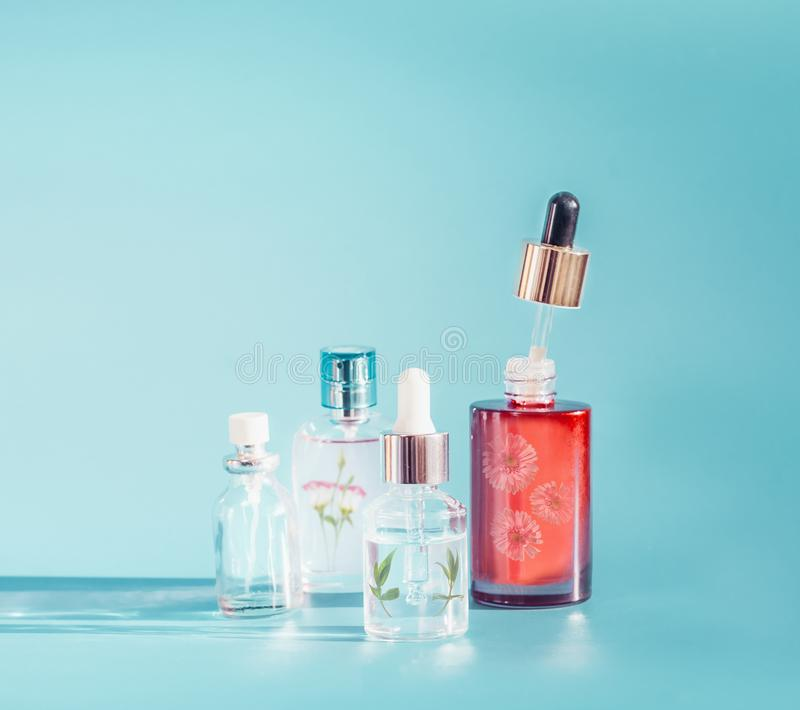 Cosmetic bottle products with liquid, pipette, herbs and flowers at blue background, front view. Floral essence or herbal extract stock images