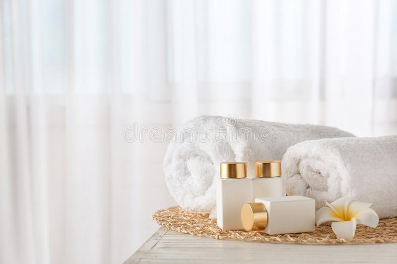 Cosmetic bottles, flower and towels on wooden table indoors, space for text. Spa treatment. Cosmetic bottles, flower and towels on white wooden table indoors royalty free stock photography