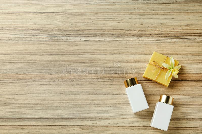 Cosmetic bottles and handmade soap on wooden table, space for text. Spa treatment. Cosmetic bottles and handmade soap on wooden table, flat lay with space for stock photo