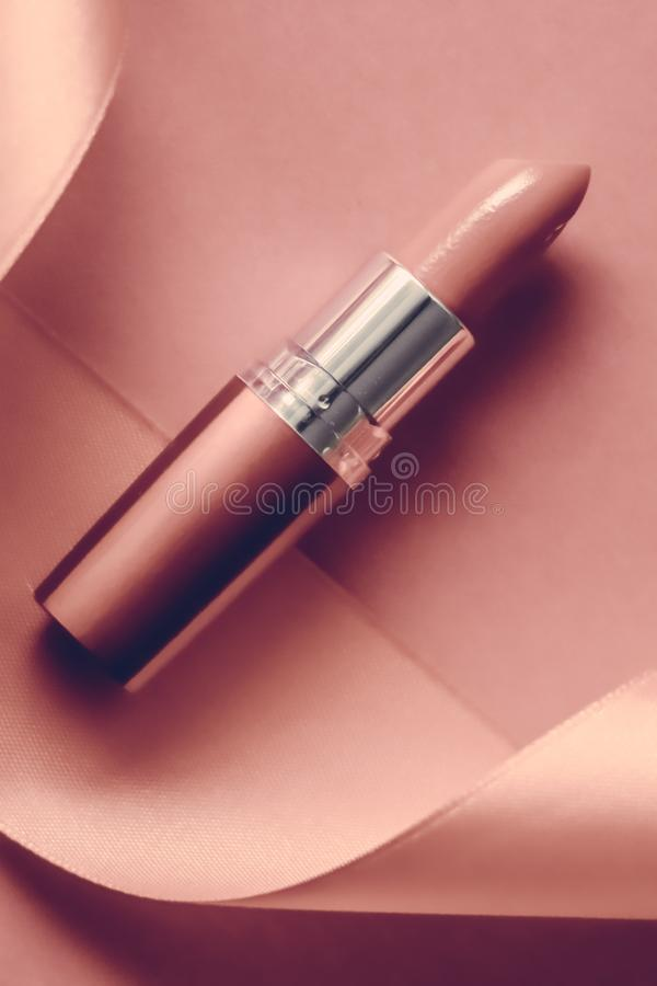 Luxury lipstick and silk ribbon on blush pink holiday background, make-up and cosmetics flatlay for beauty brand product design. Cosmetic branding, glamour lip royalty free stock photography