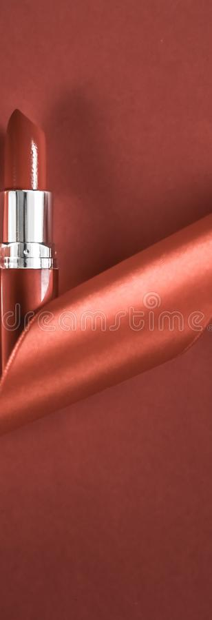 Luxury lipstick and silk ribbon on bronze holiday background, make-up and cosmetics flatlay for beauty brand product design. Cosmetic branding, glamour lip gloss stock image