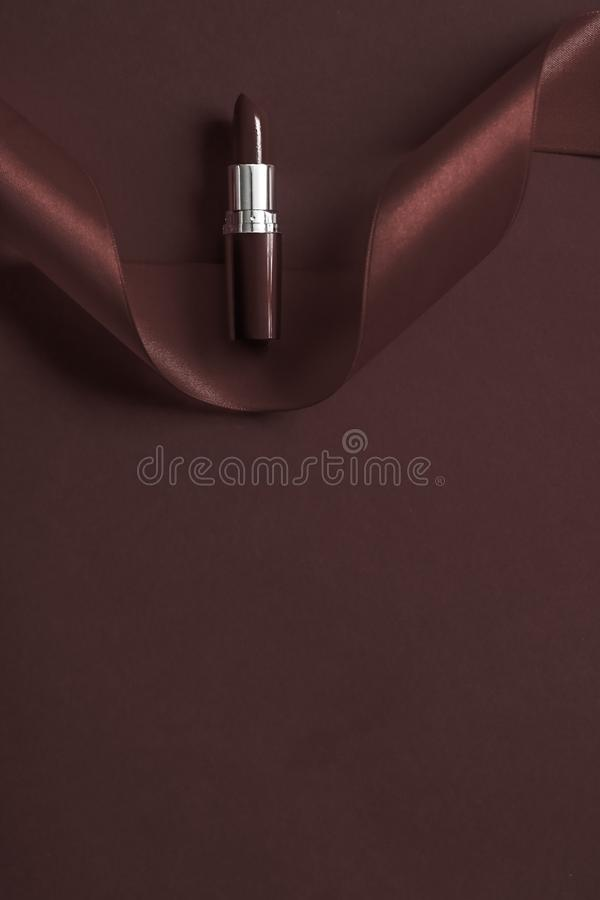 Luxury lipstick and silk ribbon on chocolate holiday background, make-up and cosmetics flatlay for beauty brand product design. Cosmetic branding, glamour lip royalty free stock photos