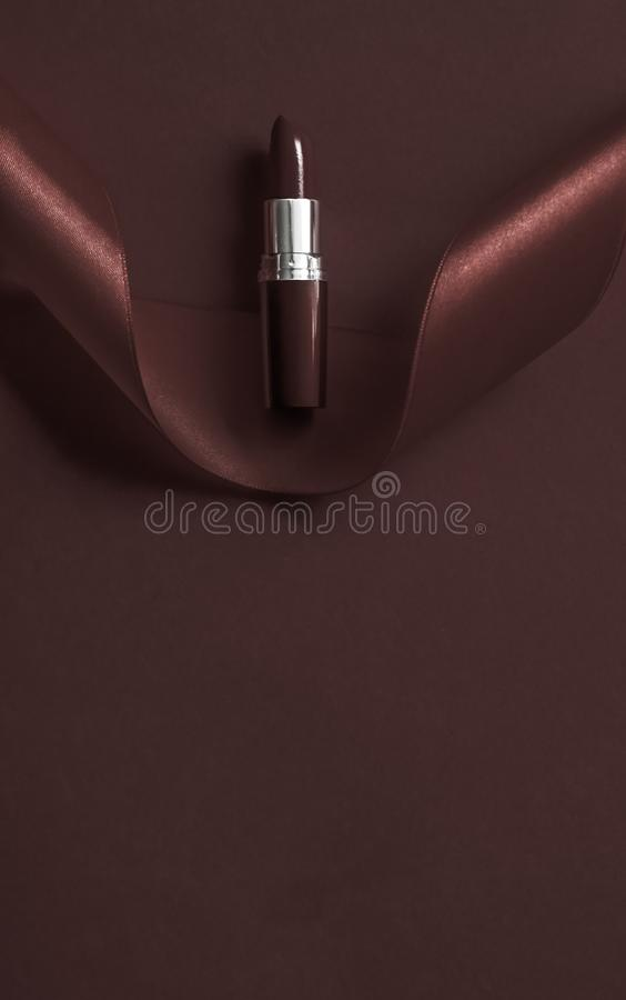 Luxury lipstick and silk ribbon on chocolate holiday background, make-up and cosmetics flatlay for beauty brand product design. Cosmetic branding, glamour lip royalty free stock image