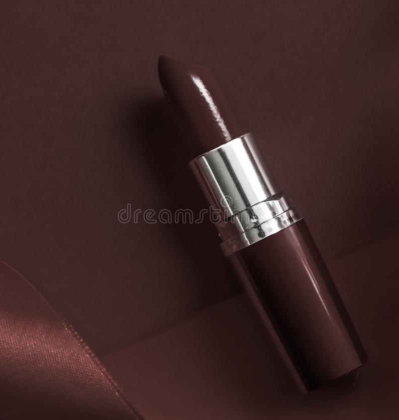 Luxury lipstick and silk ribbon on chocolate holiday background, make-up and cosmetics flatlay for beauty brand product design. Cosmetic branding, glamour lip stock photos
