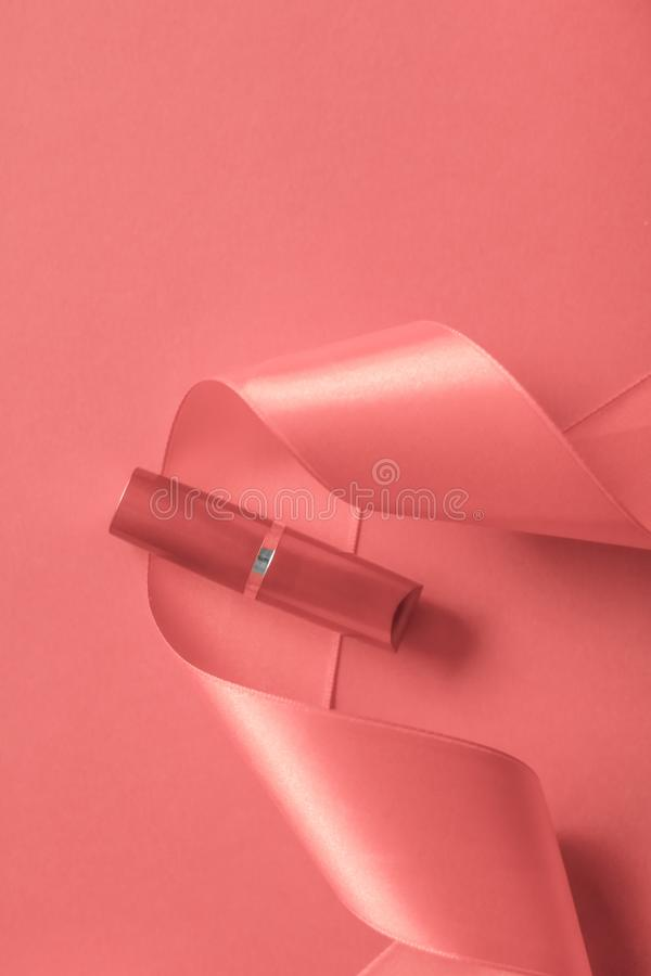 Luxury lipstick and silk ribbon on coral holiday background, make-up and cosmetics flatlay for beauty brand product design. Cosmetic branding, glamour lip gloss royalty free stock image