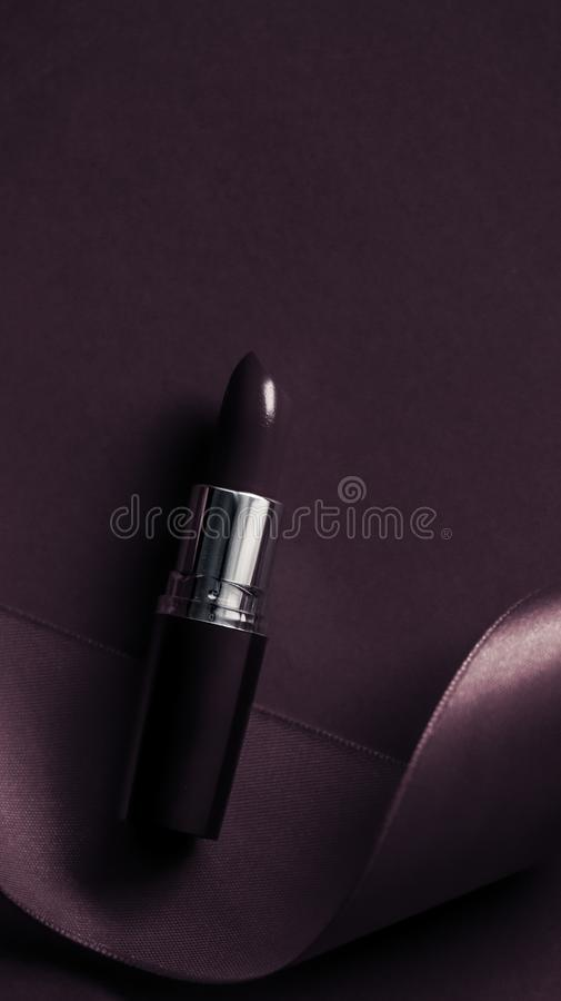 Luxury lipstick and silk ribbon on dark purple holiday background, make-up and cosmetics flatlay for beauty brand product design. Cosmetic branding, glamour lip royalty free stock image