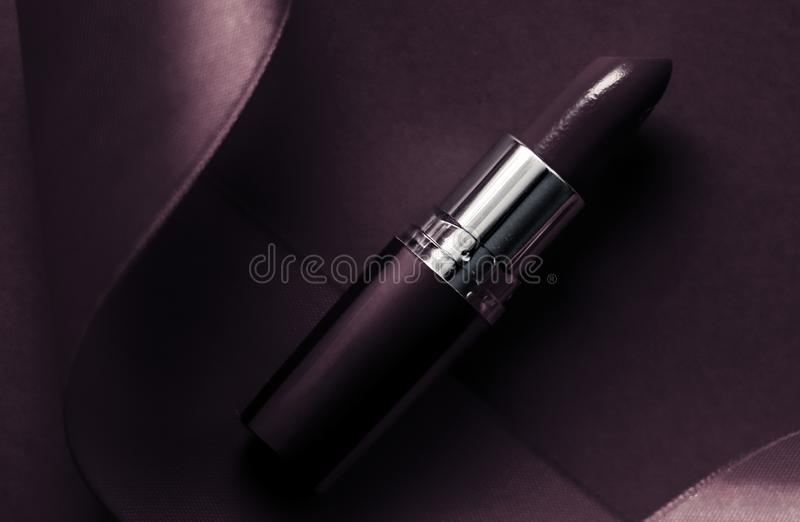 Luxury lipstick and silk ribbon on dark purple holiday background, make-up and cosmetics flatlay for beauty brand product design. Cosmetic branding, glamour lip stock images