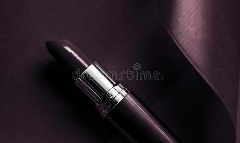 Luxury lipstick and silk ribbon on dark purple holiday background, make-up and cosmetics flatlay for beauty brand product design. Cosmetic branding, glamour lip stock photo