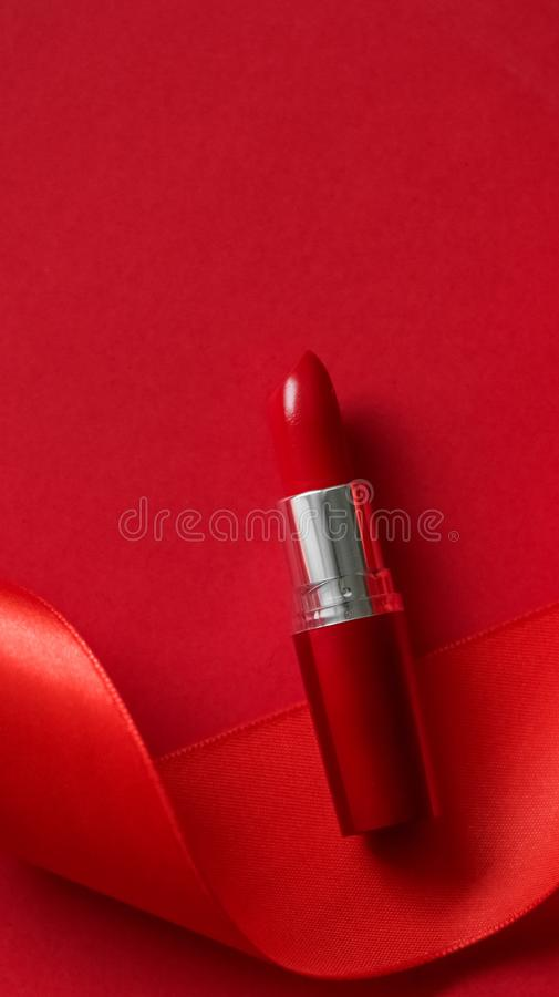 Luxury lipstick and silk ribbon on red holiday background, make-up and cosmetics flatlay for beauty brand product design. Cosmetic branding, glamour lip gloss stock image