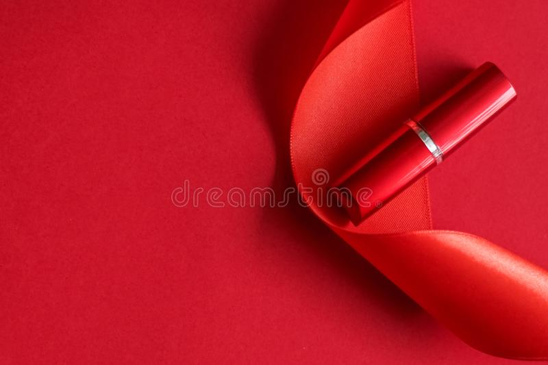 Luxury lipstick and silk ribbon on red holiday background, make-up and cosmetics flatlay for beauty brand product design. Cosmetic branding, glamour lip gloss stock photography