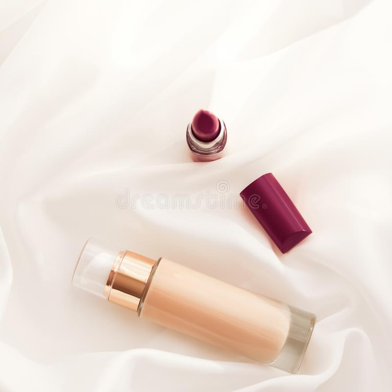 Beige tonal cream bottle make-up fluid foundation base and dark lipstick on silk background, cosmetics products as luxury beauty. Cosmetic branding, glamour and stock photos