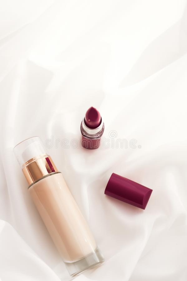 Beige tonal cream bottle make-up fluid foundation base and dark lipstick on silk background, cosmetics products as luxury beauty. Cosmetic branding, glamour and royalty free stock photography