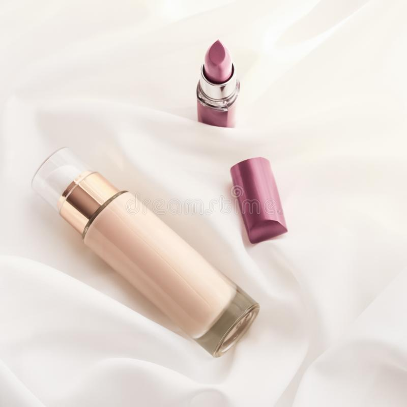 Beige tonal cream bottle make-up fluid foundation base and pink lipstick on silk background, cosmetics products as luxury beauty. Cosmetic branding, glamour and royalty free stock photography
