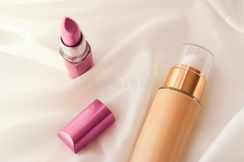 Beige tonal cream bottle make-up fluid foundation base and pink lipstick on silk background, cosmetics products as luxury beauty. Cosmetic branding, glamour and stock images