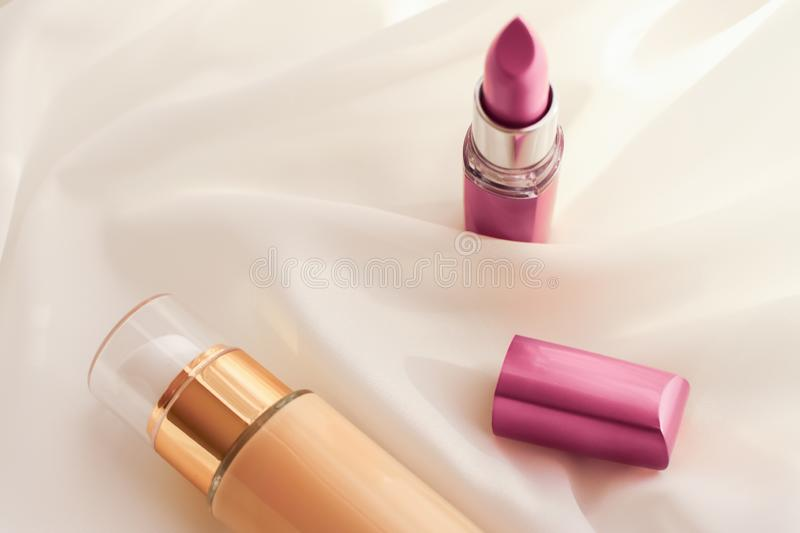 Beige tonal cream bottle make-up fluid foundation base and pink lipstick on silk background, cosmetics products as luxury beauty. Cosmetic branding, glamour and royalty free stock photo