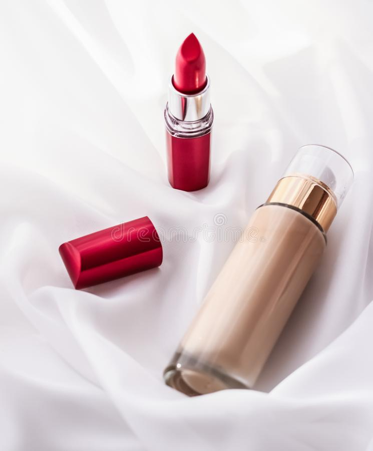 Beige tonal cream bottle make-up fluid foundation base and red lipstick on silk background, cosmetics products as luxury beauty. Cosmetic branding, glamour and stock image