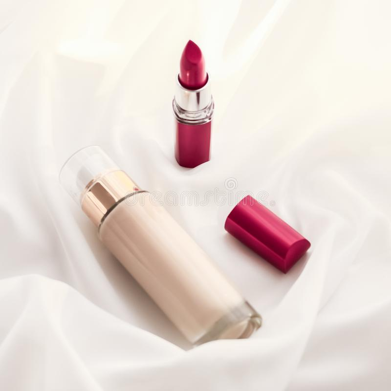Beige tonal cream bottle make-up fluid foundation base and red lipstick on silk background, cosmetics products as luxury beauty. Cosmetic branding, glamour and royalty free stock images