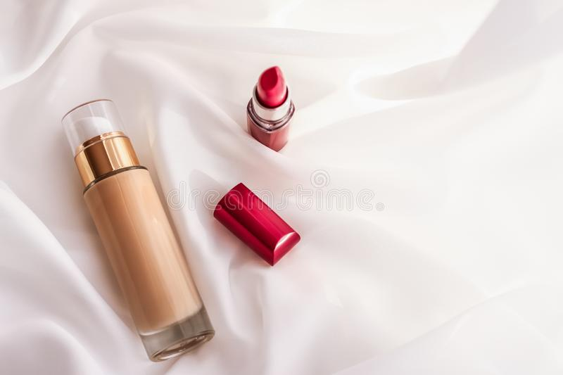 Beige tonal cream bottle make-up fluid foundation base and red lipstick on silk background, cosmetics products as luxury beauty. Cosmetic branding, glamour and stock photography