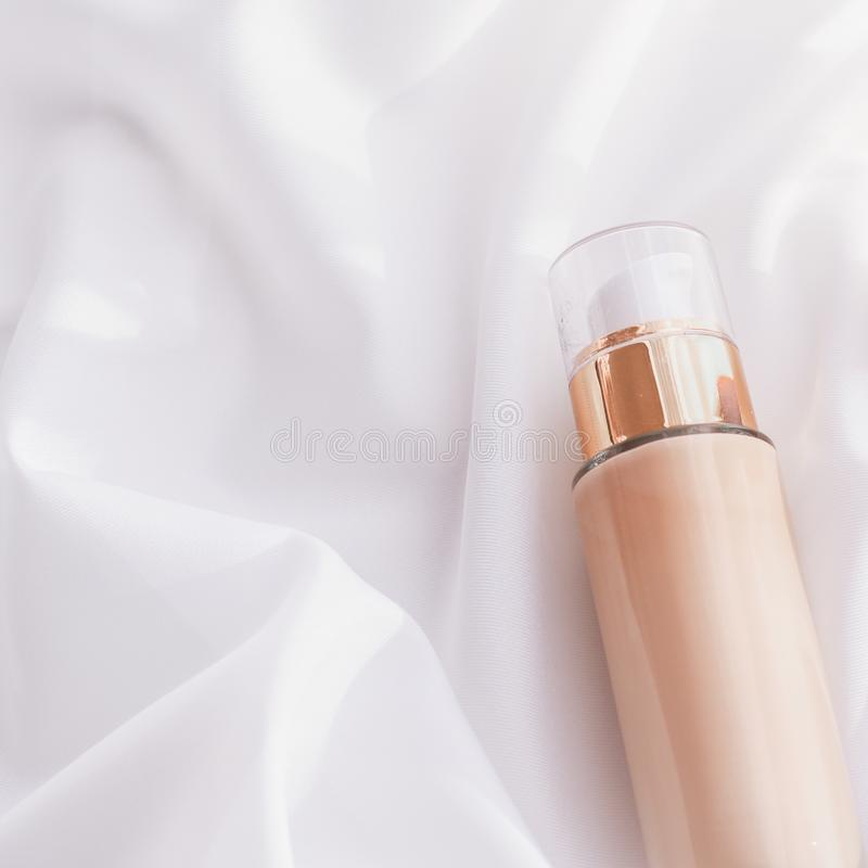 Tonal bb cream bottle make-up fluid foundation base for nude skin color on silk background, cosmetics product as luxury beauty. Cosmetic branding, glamour and stock images