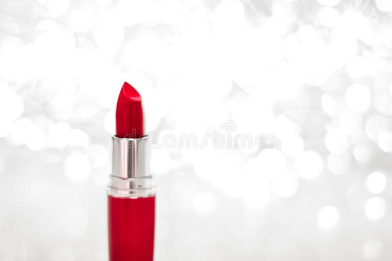 Red lipstick on silver Christmas, New Years and Valentines Day holiday glitter background, make-up and cosmetics product for. Cosmetic branding, sale and glamour stock photos