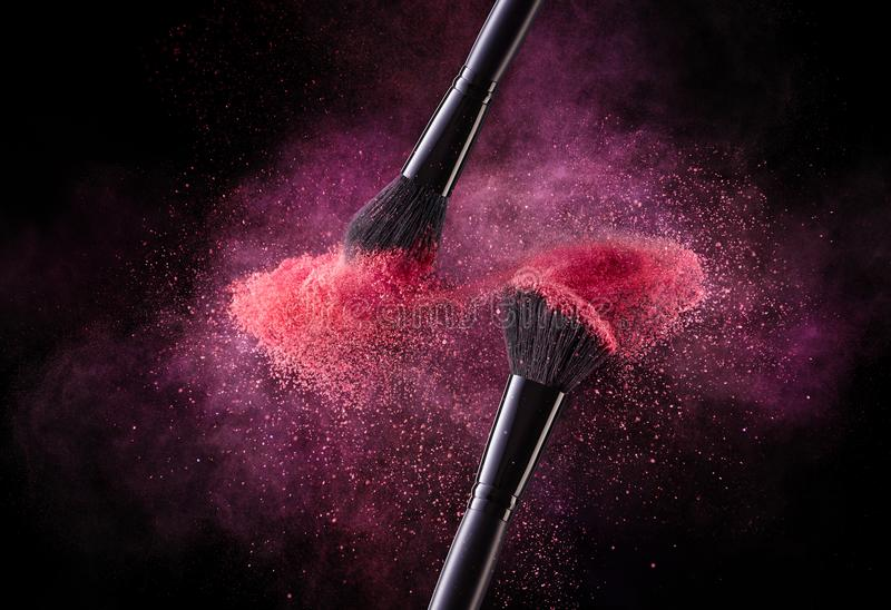 Cosmetic Brushes And Explosion Colorful Powders. royalty free stock image