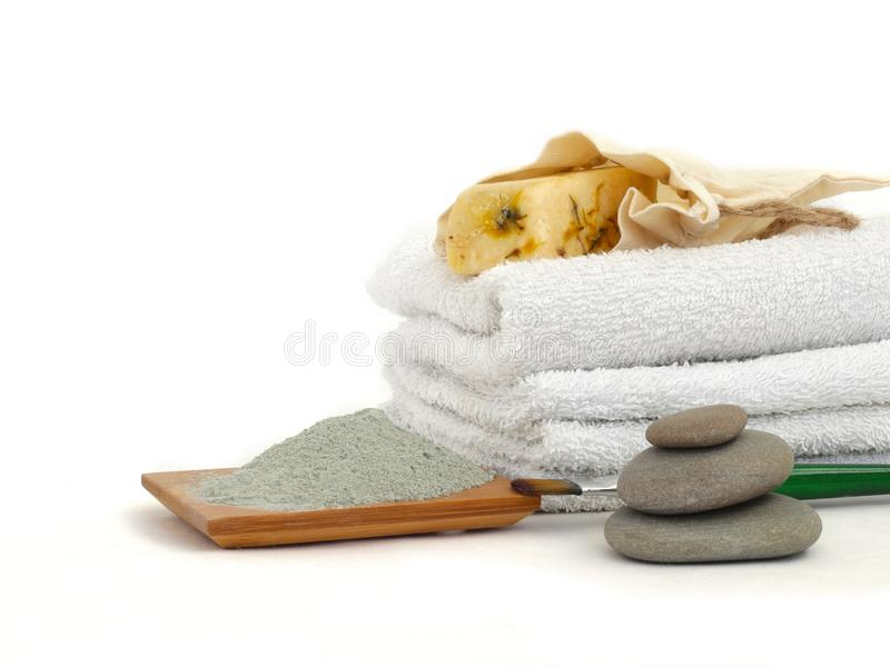 Cosmetic clay on wooden plate. Natural ingredients for homemade spa and skin detox. Cotton towels and handmade soap with flower. Leafes for face cleancing royalty free stock image