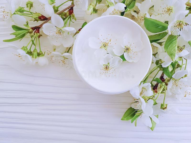 Cosmetic cream blooming cherry beauty health ointmenton a white wooden background royalty free stock image