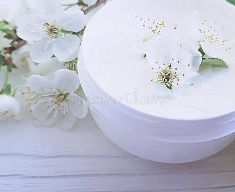 Cosmetic cream blooming cherry health ointmenton a white wooden background royalty free stock image