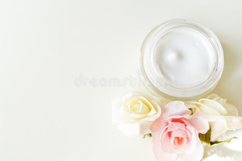 Cosmetic cream with herbal flowers on white table with copy space . natural product .skin body care concept stock photos