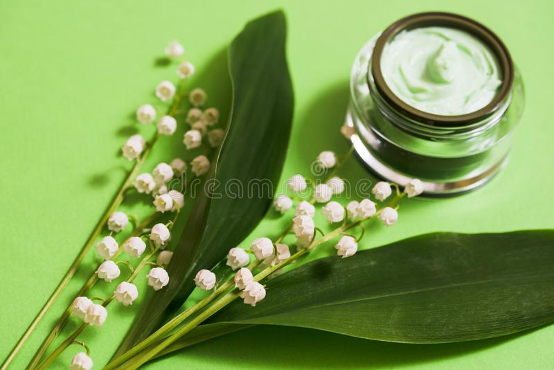 cosmetic cream and lily of the valley flowers on a green background. stock photo