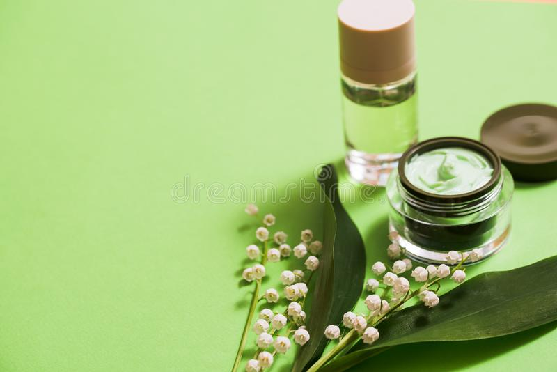 cosmetic cream and lily of the valley flowers on a green background. stock image