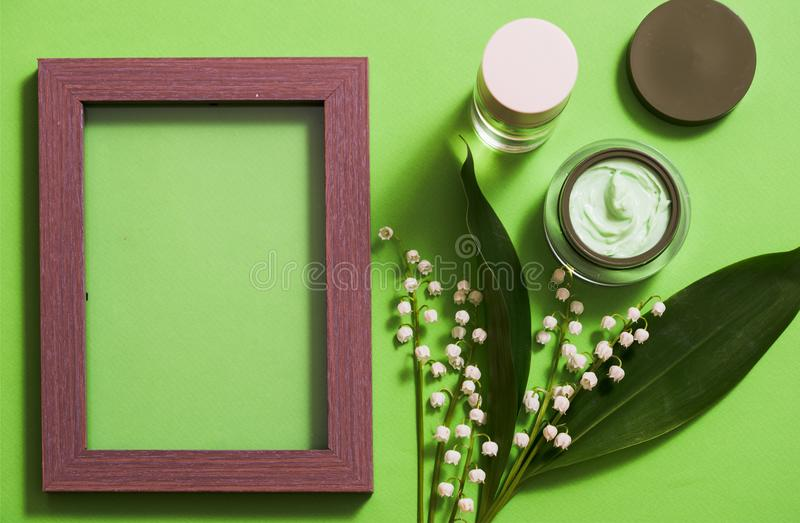 cosmetic cream and lily of the valley flowers on a green background. stock photography