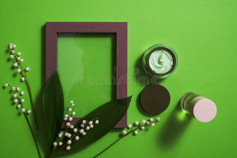cosmetic cream and lily of the valley flowers on a green background. stock images