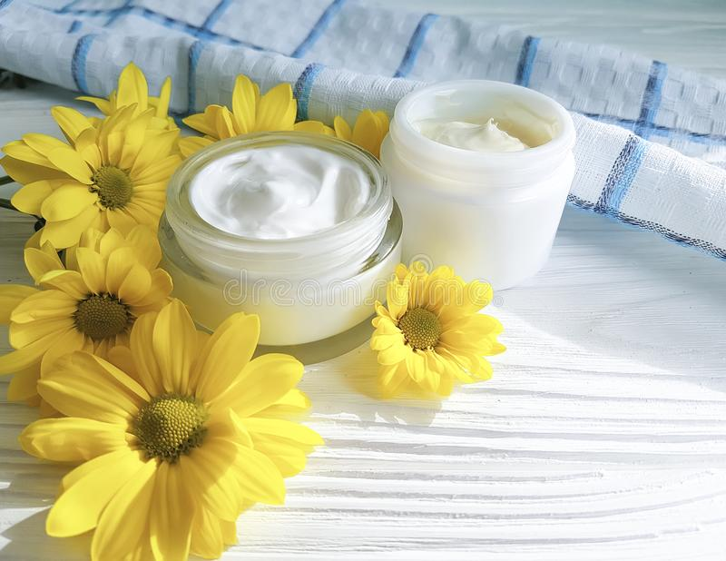 Cosmetic cream organic morning skincare a jar yellow chrysanthemum flower white wooden, daisy, towel. Cosmetic organic cream in a jar yellow chrysanthemum flower stock images
