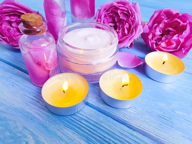Cosmetic cream, pink rose extract on wooden background, candle stock photo